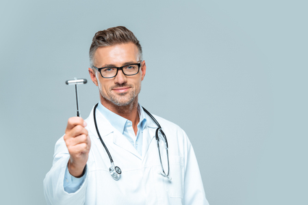 handsome neurologist with stethoscope on shoulders showing reflex hammer isolated on white Banco de Imagens