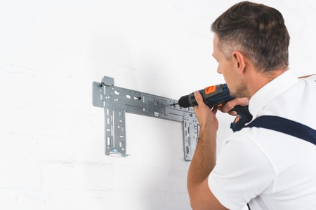 adult foreman installing bracket for air conditioner with drill