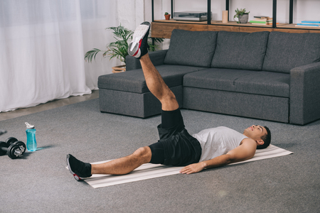 bi-racial athlete doing exercise on legs while lying on  fitness mat