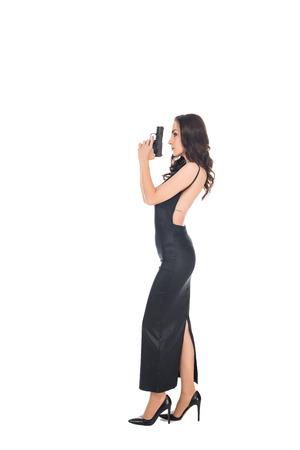beautiful female killer in black dress holding gun, isolated on white