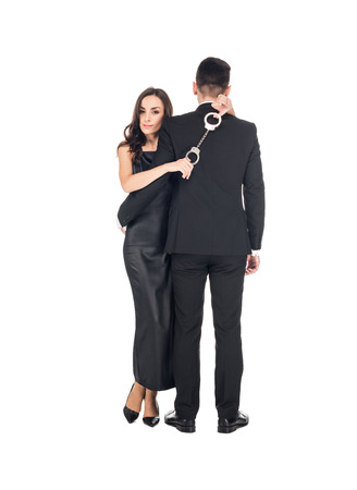 elegant woman in black dress hugging man and holding handcuffs, isolated on white