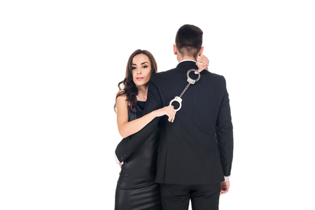 attractive girl hugging man and holding handcuffs, isolated on white