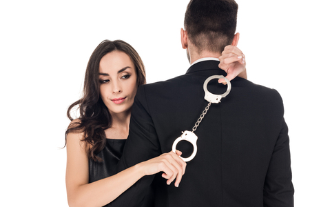 beautiful woman hugging man and holding handcuffs, isolated on white Stock Photo