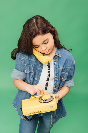 cute child talking on yellow vintage telephone isolated on green Stock fotó - 117334563