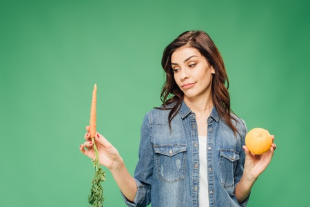 skeptical woman in denim choosing between orange and carrot isolated on green