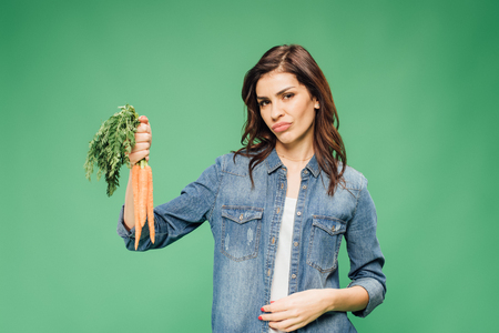 skeptical woman holding carrots and looking at camera isolated on green