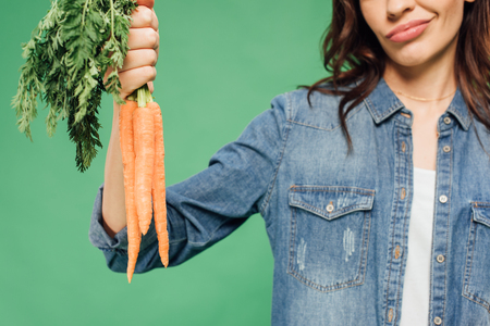 cropped view of skeptical woman in denim holding carrots isolated on green