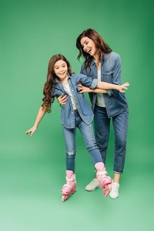 lächelnde Mutter, die Tochter Rollerblading auf grünem Hintergrund beibringt Standard-Bild