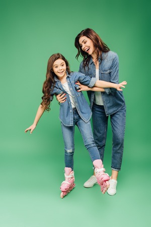 smiling mother teaching daughter rollerblading on green background Foto de archivo