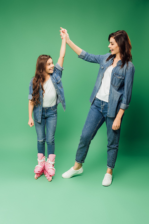 happy daughter in rollerblading cheering and holding hands with mother on green background