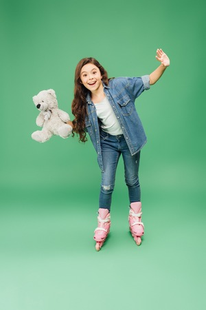 child rollerblading with outstretched hands and teddy bear on green background Stock Photo