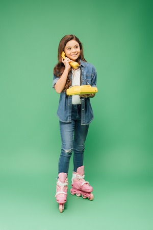 smiling child in roller blades talking on vintage telephone on green background