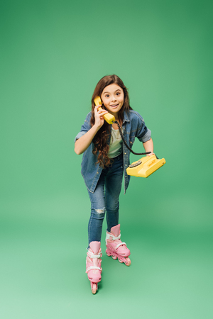 child rollerblading and talking on vintage telephone on green background