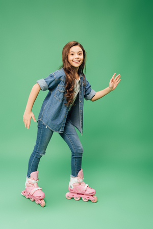 smiling child rollerblading with outstretched hands on green background
