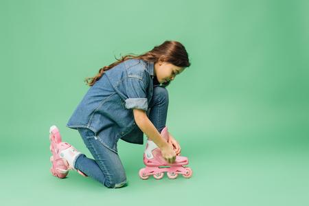 child in denim putting on roller blades on green background Stock Photo