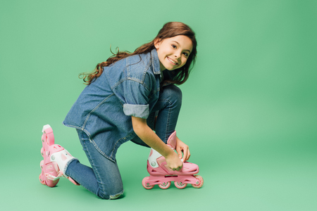 cute child putting on rollerskates and looking at camera on green background Stock Photo