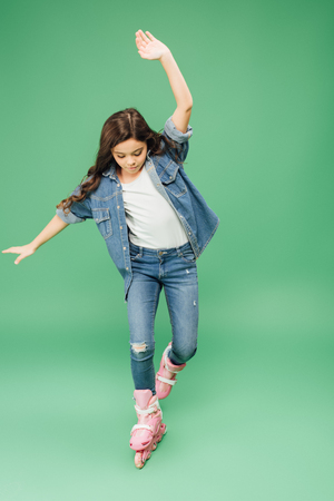 child in denim rollerblading with outstretched hands on green background