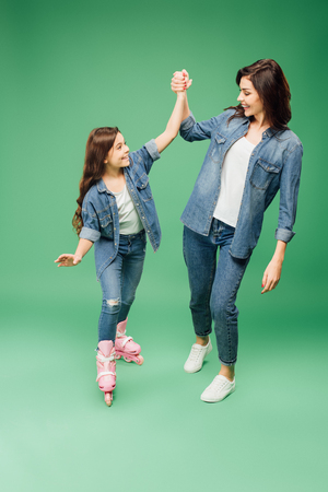 happy daughter in rollerskates holding hands and cheering with mother on green background