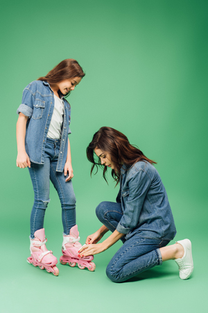 mother in denim putting roller blades on daughter on green background Stock Photo
