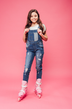 smiling child in overalls and roller blades looking at camera on pink background
