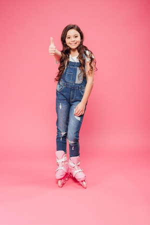 child in overalls and rollerskates showing thumb up sign on pink background Stock Photo