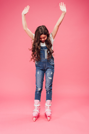 child in overalls rollerblading with outstretched hands on pink background