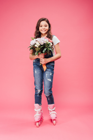 adorable smiling child in rollerskates with flower bouquet on pink background