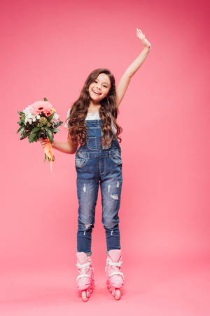 adorable smiling child in roller blades with flower bouquet raising hand on pink background