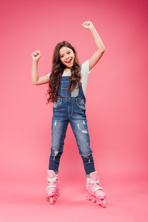 happy child in overalls and rollerskates cheering with arms in air on pink background