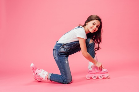 cute child in overalls putting on rollerskates on pink background Stock fotó