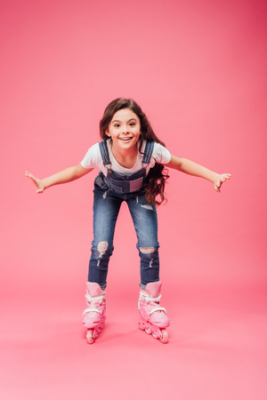 happy child in overalls rollerblading on pink background