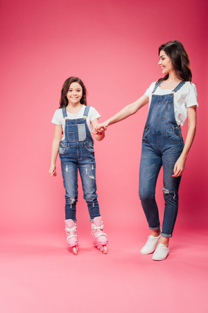 beautiful smiling daughter in roller blades holding hands with mother on pink background