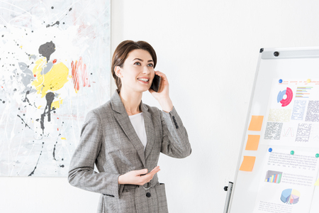 attractive businesswoman in grey suit standing near flipchart and talking by smartphone in office