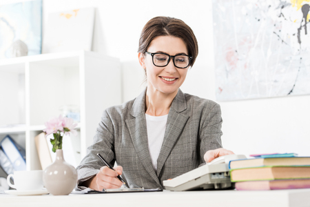 surface level of smiling attractive businesswoman answering stationary telephone in office