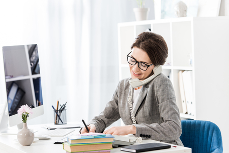 smiling attractive businesswoman talking by stationary telephone in office Stock Photo