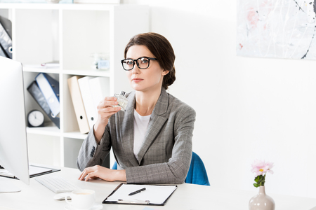attractive businesswoman sniffing jar of perfume in office Imagens