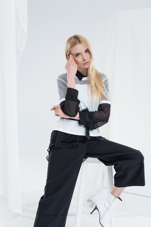 beautiful caucasian blonde woman in fashionable black clothes sitting on chair and touching face isolated on white