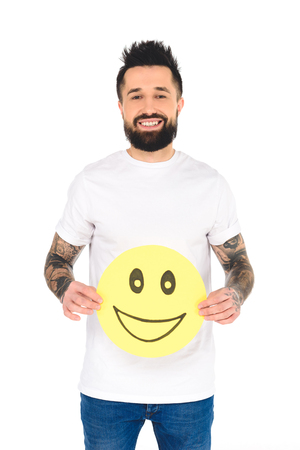 handsome bearded man with tattoos holding yellow card with happy face expression while looking at camera isolated on white Imagens