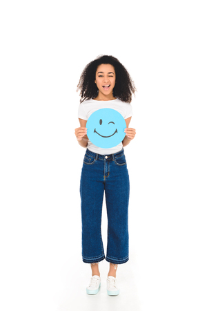 african american girl holding round, blue sign with winking face expression and smiling at camera isolated on white