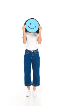 african american girl holding round sign with winking face expression isolated on white