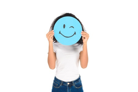 african american girl holding round, blue sign with winking face expression isolated on white
