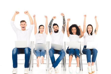 multicultural group of people using laptops and rejoicing with hands above head isolated on white