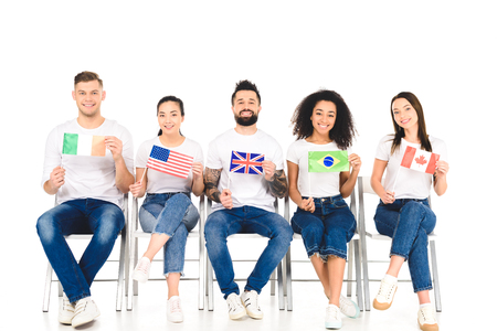 multicultural group of people sitting on chairs with flags of different countries isolated on white Stock Photo