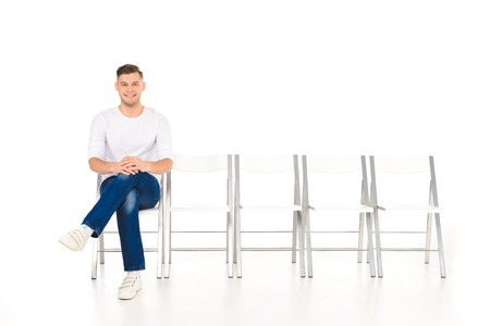 handsome young man sitting with crossed legs isolated on white