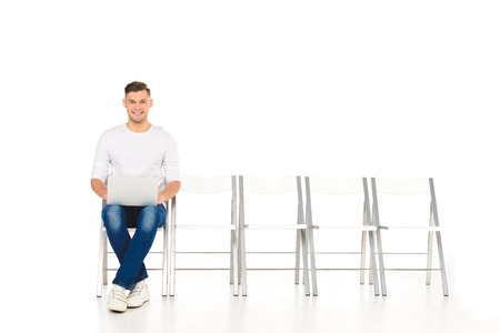 handsome young man sitting with crossed legs and laptop isolated on white