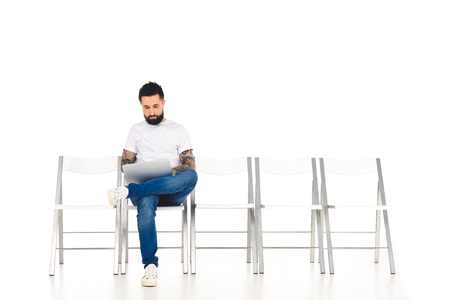 handsome bearded man using laptop isolated on white