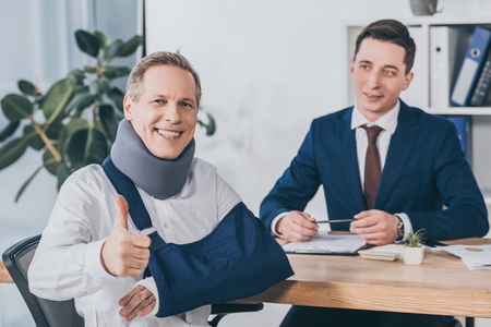 businessman sitting at table wile worker in neck brace and arm bandage showing thumb up in office, compensation concept