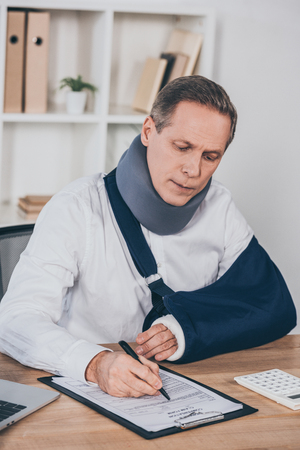 worker in neck brace and arm bandage sitting at table and writing with pen in office, compensation concept