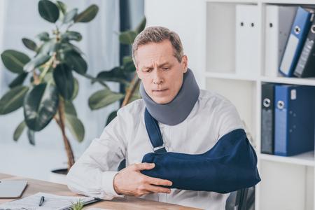 Arbeiter mittleren Alters, der einen gebrochenen Arm hält, während er mit Dokument im Büro am Tisch sitzt, Vergütungskonzept
