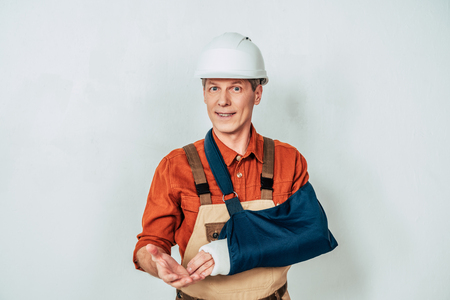repairman with arm bandage standing on white background Stock Photo